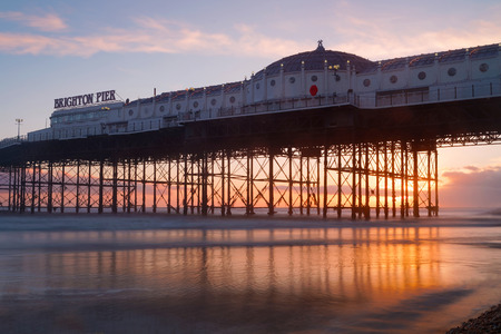 Brighton pier at sunset, warm red and orange colors. The pier reflecting in the water
