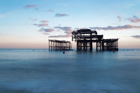 Abandoned West pier in Brighton at sunset, warm blue colors. Soft water in the foreground