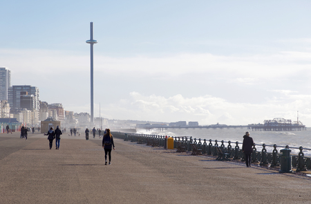 People walking on the boardwalk between Brighton and Hove, the attraction British Airways i360 in the background