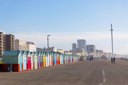 Lots of very colorful bathing huts in Brighton and Hove and people walking, the attraction British Airways i360 in the background