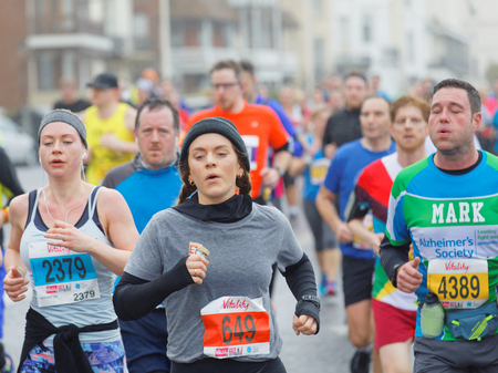 brighton: BRIGHTON, GREAT BRITAIN - FEB 26, 2017: Young  girl and competitors running in the Vitality Brighton half marathon competition. February 26, 2017 in Brighton, Great Britain