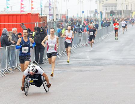 BRIGHTON, GREAT BRITAIN - FEB 26, 2017: Man i sports wheelchair and running competitiors in the Vitality Brighton half marathon competition. February 26, 2017 in Brighton, Great Britain