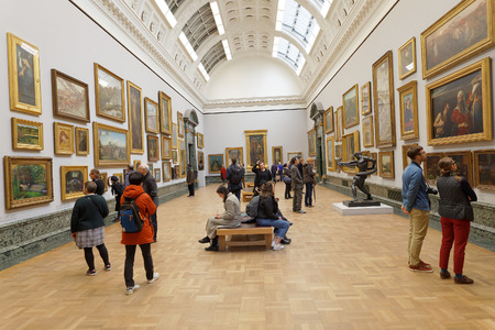 LONDON, GREAT BRITAIN - FEB 27, 2017: Interior of the museum Tate Britain. People watching paintings. February 27, 2017 in London, Great Britain