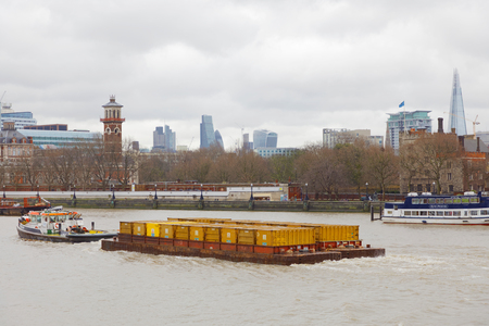 LONDON, GREAT BRITAIN - FEB 27, 2017: Towboat tow many yellow containers on the river Thames. February 27, 2017 in London, Great Britain