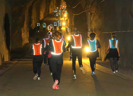 STOCKHOLM, SWEDEN - MAR 25, 2017: Rear view of many runners in reflex vest in a dark tunnel in the Stockholm Tunnel Run Citybanan 2017. March 25, 2017 in Stockholm, Sweden