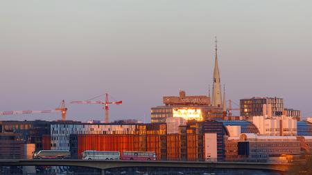 STOCKHOLM, SWEDEN - APR 30, 2017:Buildings in beautiful copper color in central Stockholm in the warm evening light and buses on the bridge Barnhusbron, April 30, 2017 in Stockholm, Sweden