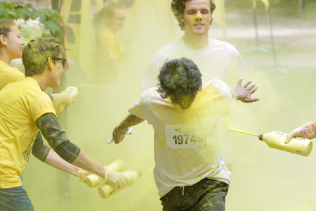 squirted: STOCKHOLM, SWEDEN - MAY 22, 2016: Smiling boys  getting squirted with yellow color dust in their face and clothes in the Color Run Event in Sweden, May 22, 2016 Editorial
