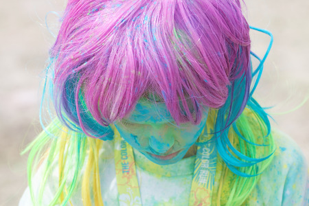 STOCKHOLM, SWEDEN - MAY 22, 2016: Girl with colorful wig covered with color dust looking down in the Color Run Event in Sweden, May 22, 2016 Editorial
