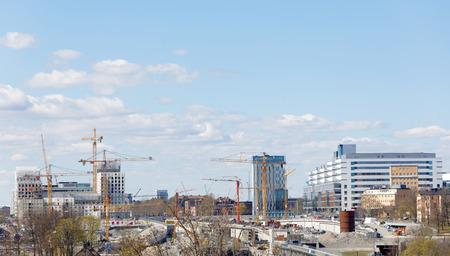 buildingsite: STOCKHOLM, SWEDEN - MAY 01, 2017: Cranes building houses in the new district New Hagastaden and the hospital Nya Karolinska in Stockholm. May 01, 2017 in Stockholm, Sweden