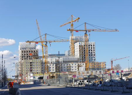 buildingsite: STOCKHOLM, SWEDEN - MAY 01, 2017: Cranes building houses in the new district New Hagastaden in Stockholm. May 01, 2017 in Stockholm, Sweden