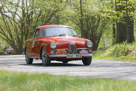 restore: STOCKHOLM, SWEDEN - MAY 22, 2017: Red Alfa Romeo Guiletta classic car from 1960 driving on a country road in the public race Gardesloppet in the forests at Djurgarden, Stockholm, Sweden. May 22, 2017