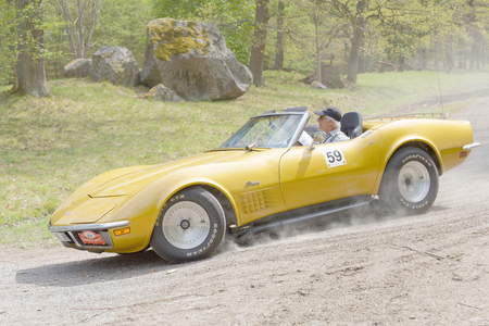 STOCKHOLM, SWEDEN - MAY 22, 2017: Yellow Chevrolet Corvette Stingray classic car from 1971 driving on a country road in the public race Gardesloppet in the forests at Djurgarden, Stockholm, Sweden. May 22, 2017