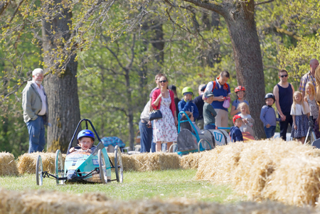 STOCKHOLM, SWEDEN - MAY 21, 2017: Concentrated little girl driving a home made soapbox car downhill on a field in the race Gardesloppet at Djurgarden, Stockholm, Sweden. May 21, 2017