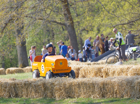 STOCKHOLM, SWEDEN - MAY 21, 2017: Boy driving a home made soapbox car downhill on a field, people in the background in the race Gardesloppet at Djurgarden, Stockholm, Sweden. May 21, 2017 Editorial