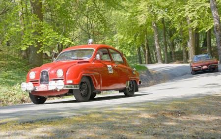chrome man: STOCKHOLM, SWEDEN - MAY 22, 2017: Red SAAB 96 classic car from 1964 driving on a country road in the public race Gardesloppet in the forests at Djurgarden, Stockholm, Sweden. May 22, 2017 Editorial