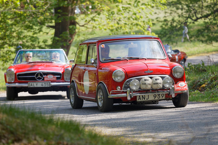 STOCKHOLM, SWEDEN - MAY 22, 2017: Red Austin Cooper and a Mercedes classic car in a slope in the public race Gardesloppet in the beautiful forests in Djurgarden in Stockholm. May 22, 2017 in Stockholm, Sweden