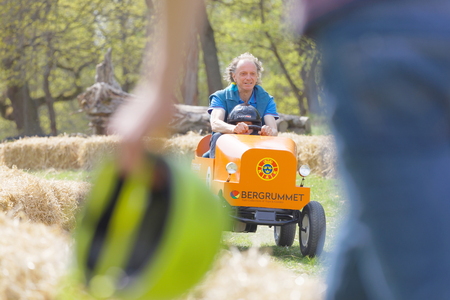 STOCKHOLM, SWEDEN - MAY 21, 2017: Smiling boy and granpa driving a orange soapbox car downhill on a field in the race Gardesloppet at Djurgarden, Stockholm, Sweden. May 21, 2017