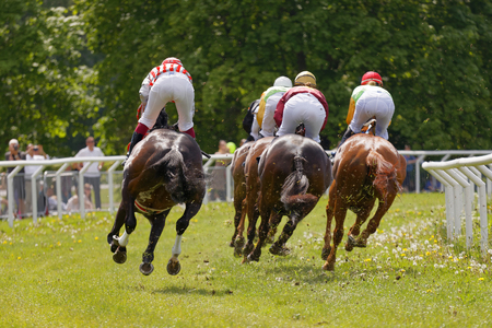 hippodrome: STOCKHOLM, SWEDEN - JUNE 06, 2017: Rear view of standing colorful jockeys on race horses riding in a curve at Nationaldags Galoppen at Gardet. June 6, 2017 in Stockholm, Sweden