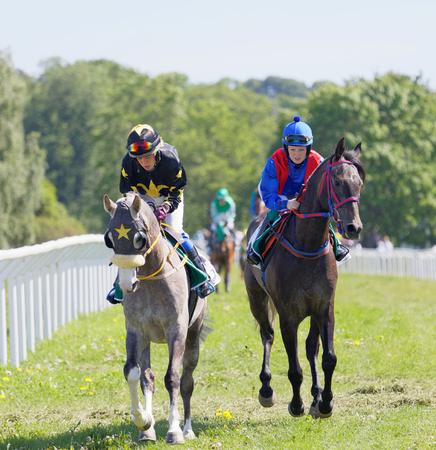 racetrack: STOCKHOLM, SWEDEN - JUNE 06, 2017: Two female jockeys riding arabian race horses after the gallop race at Nationaldags Galoppen at Gardet. June 6, 2017 in Stockholm, Sweden