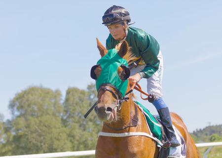 racetrack: STOCKHOLM, SWEDEN - JUNE 06, 2017: Closeup of a female jockey riding a brown arabian race horse at Nationaldags Galoppen at Gardet. June 6, 2017 in Stockholm, Sweden Editorial