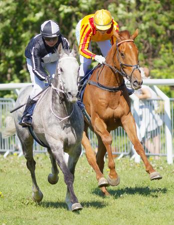 STOCKHOLM, SWEDEN - JUNE 06, 2017: Two jockeys side by side riding gallop arabian race horses at Nationaldags Galoppen at Gardet. June 6, 2017 in Stockholm, Sweden Editorial
