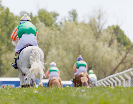 STOCKHOLM, SWEDEN - JUNE 06, 2017: Rear view of young kids riding cute ponys at Nationaldags Galoppen at Gardet. June 6, 2017 in Stockholm, Sweden Editorial