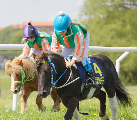 rival: STOCKHOLM, SWEDEN - JUNE 06, 2017: Two young jockey girls riding cute ponys at Nationaldags Galoppen at Gardet. June 6, 2017 in Stockholm, Sweden