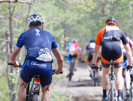 STOCKHOLM, SWEDEN - JUNE 11, 2017: Rear view of group of mountain bike cyclists in the forest at Lida Loop Mountain bike Race. June 11, 2017 in Stockholm, Sweden
