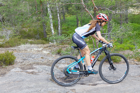 elite: STOCKHOLM, SWEDEN - JUNE 11, 2017: Side view of female mountain bike cyclist in the forest on a rock at Lida Loop Mountain bike Race. June 11, 2017 in Stockholm, Sweden