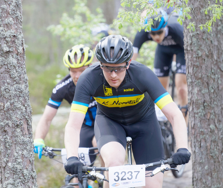 elite: STOCKHOLM, SWEDEN - JUNE 11, 2017: Closeup of group of mountain bike cyclists in the forest at Lida Loop Mountain bike Race. June 11, 2017 in Stockholm, Sweden