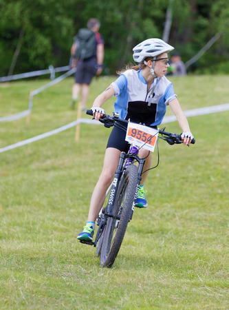 STOCKHOLM, SWEDEN - JUNE 11, 2017: Mountain bike cyclist girl in downhill on the grass at Lida Loop Mountain bike Race. June 11, 2017 in Stockholm, Sweden