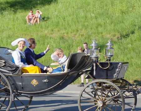 STOCKHOLM, SWEDEN - JUN 06, 2017: The swedish crown princess Victoria, prince Daniel and princess Estelle Bernadotte smiling and waiving to the audience from the royal coach on their way to celebrate the swedish national day.