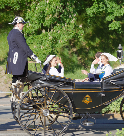 carl: STOCKHOLM, SWEDEN - JUN 06, 2017: The swedish princess and prince Sofia and Carl Philip, Madeleine and Chris Bernadotte smiling and waiving to the audience from the royal coach on their way to celebrate the swedish national day.