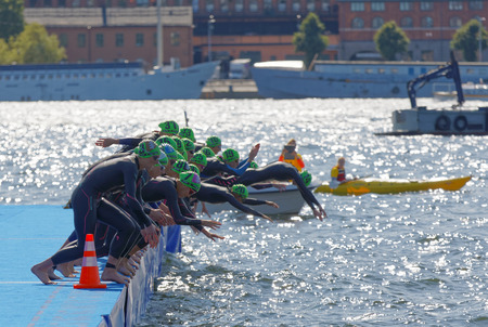 STOCKHOLM - AUG 26, 2017: The female swimming competitors wearing black swimsuits jump into the water after the start signal in the Womens ITU World Triathlon series event August 22, 2017 in Stockholm, Sweden Editorial