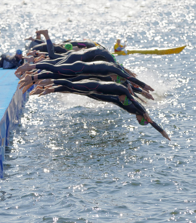 STOCKHOLM - AUG 26, 2017: The female competitors wearing green bathing cap jump into the water after the start signal in the Womens ITU World Triathlon series event August 22, 2017 in Stockholm, Sweden Editorial
