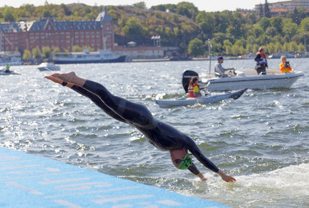 STOCKHOLM - AUG 26, 2017: Female swimmer wearing black swimsuit  jump into the water in the Womens ITU World Triathlon series event August 22, 2017 in Stockholm, Sweden