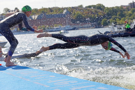 STOCKHOLM - AUG 26, 2017: Two female swimmer wearing black swimsuit  jump into the water in the Womens ITU World Triathlon series event August 22, 2017 in Stockholm, Sweden