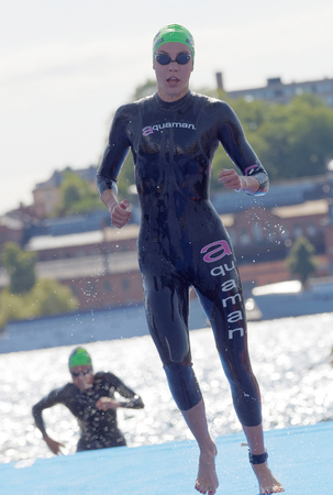 STOCKHOLM - AUG 26, 2017: Female triathlete swimmers wearing black swimsuits climbing up from the water in the Womens ITU World Triathlon series event August 22, 2017 in Stockholm, Sweden