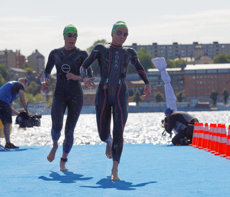 STOCKHOLM - AUG 26, 2017: Female triathlete swimmers wearing black swimsuits running up from the water in the Womens ITU World Triathlon series event August 22, 2017 in Stockholm, Sweden