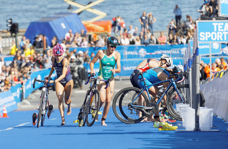 STOCKHOLM - AUG 26, 2017: Female triathletes Spivey, Van Coevorden and compryitors running with cycles and competitors in the transition zone in the Womens ITU World Triathlon series event August 26, 2017 in Stockholm, Sweden
