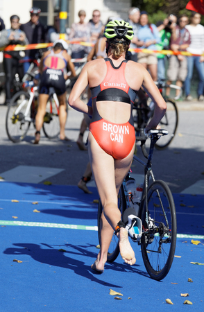 STOCKHOLM - AUG 26, 2017: Back of female triathlete Joanna Brown (CAN) and competitors running with cycle in the transition zone in the Womens ITU World Triathlon series event August 26, 2017 in Stockholm, Sweden