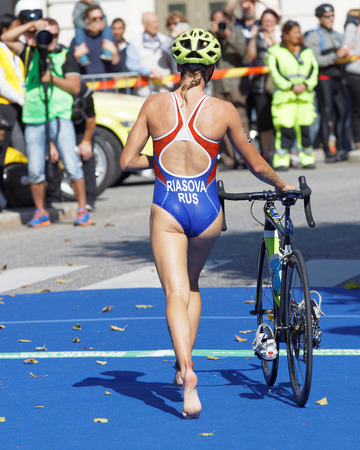 STOCKHOLM - AUG 26, 2017: Back of triathlete Valentina Riasova (RUS) running with cycle in the transition zone in the Womens ITU World Triathlon series event August 26, 2017 in Stockholm, Sweden