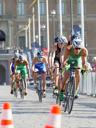 elite: STOCKHOLM - AUG 26, 2017: Back of group of colorful triathlete cyclists in the Mens ITU World Triathlon series event August 26, 2017 in Stockholm, Sweden Editorial