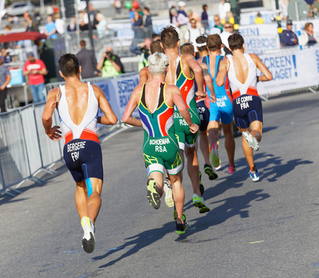 elite: STOCKHOLM - AUG 26, 2017: Back of colorful group of running triathletes, Bergere, Schoeman and competitors in the Mens ITU World Triathlon series event August 26, 2017 in Stockholm, Sweden