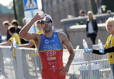 elite: STOCKHOLM - AUG 26, 2017: Running triathlete Vincente Hernandez (ESP) splashing water from a bottle in his face in the Mens ITU World Triathlon series event August 26, 2017 in Stockholm, Sweden
