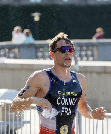 elite: STOCKHOLM - AUG 26, 2017: Running triathlete Dorian Coninx (FRA) splashing water from a bottle over his body in the Mens ITU World Triathlon series event August 26, 2017 in Stockholm, Sweden