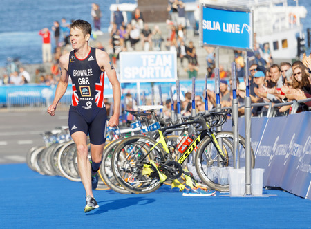 elite: STOCKHOLM - AUG 26, 2017: Running triathletes Jonathan Brownlee realize he is going to win the race in the Mens ITU World Triathlon series event August 26, 2017 in Stockholm, Sweden Editorial