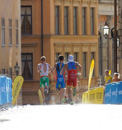elite: STOCKHOLM - AUG 26, 2017: Rear view of running triathlete Hernandez, Gundersen and White in the old town in Stockholm in the Mens ITU World Triathlon series event August 26, 2017 in Stockholm, Sweden