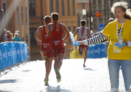 elite: STOCKHOLM - AUG 26, 2017: Rear view of running triathlete Fridelance and Briford in the old town in Stockholm in the Mens ITU World Triathlon series event August 26, 2017 in Stockholm, Sweden