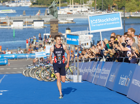 elite: STOCKHOLM - AUG 26, 2017: Running triathletes Jonathan Brownlee and smiling hand clapping audience  in the background in the Mens ITU World Triathlon series event August 26, 2017 in Stockholm, Sweden